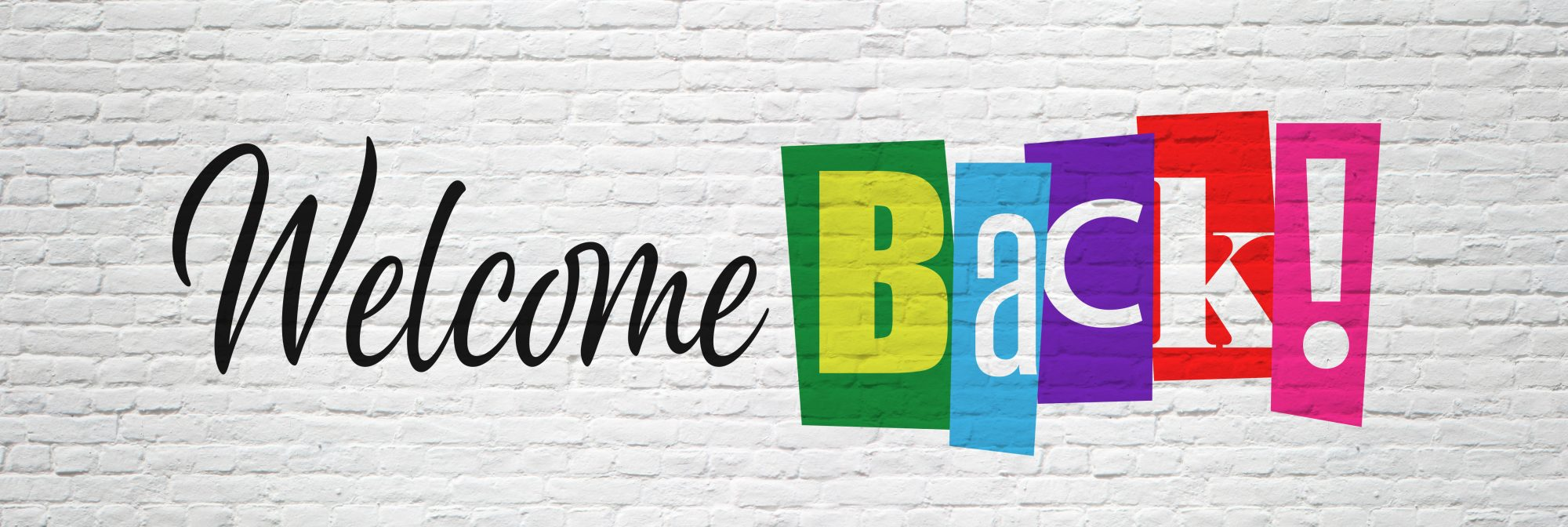 Bunter Welcome Back Schriftzug auf Backsteinmauer
