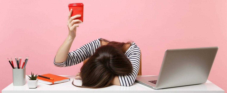 Stress am Arbeitsplatz: erschöpfte Frau legte ihren Kopf auf den Tisc
